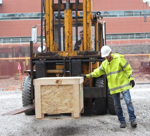 Fork lift moving crate into Sweeney