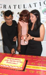 Russell Mahmood with students cutting cake